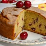 Fresh Cherry Cake, with a slice removed, on a patterned plate