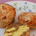 Two cheese scones on a flowered plate on a pink tablecloth. One cheese scone is split in two with one half buttered. The other scone is whole.