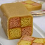 Easy Battenberg Cake on a white plate with 2 slices cut
