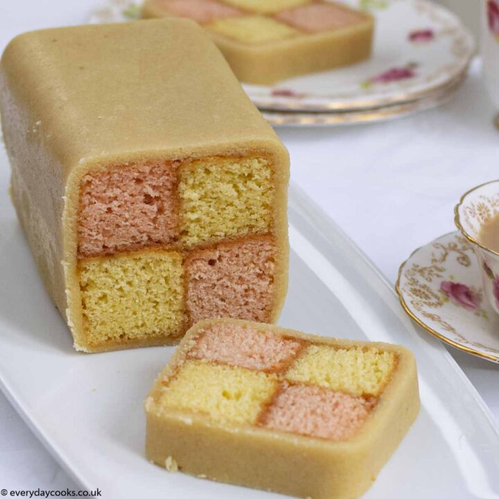 Easy Battenberg Cake on a white plate with 2 slices cut, with a cup of tea.