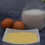 Bowl of homemade custard with 2 eggs and a jug of milk
