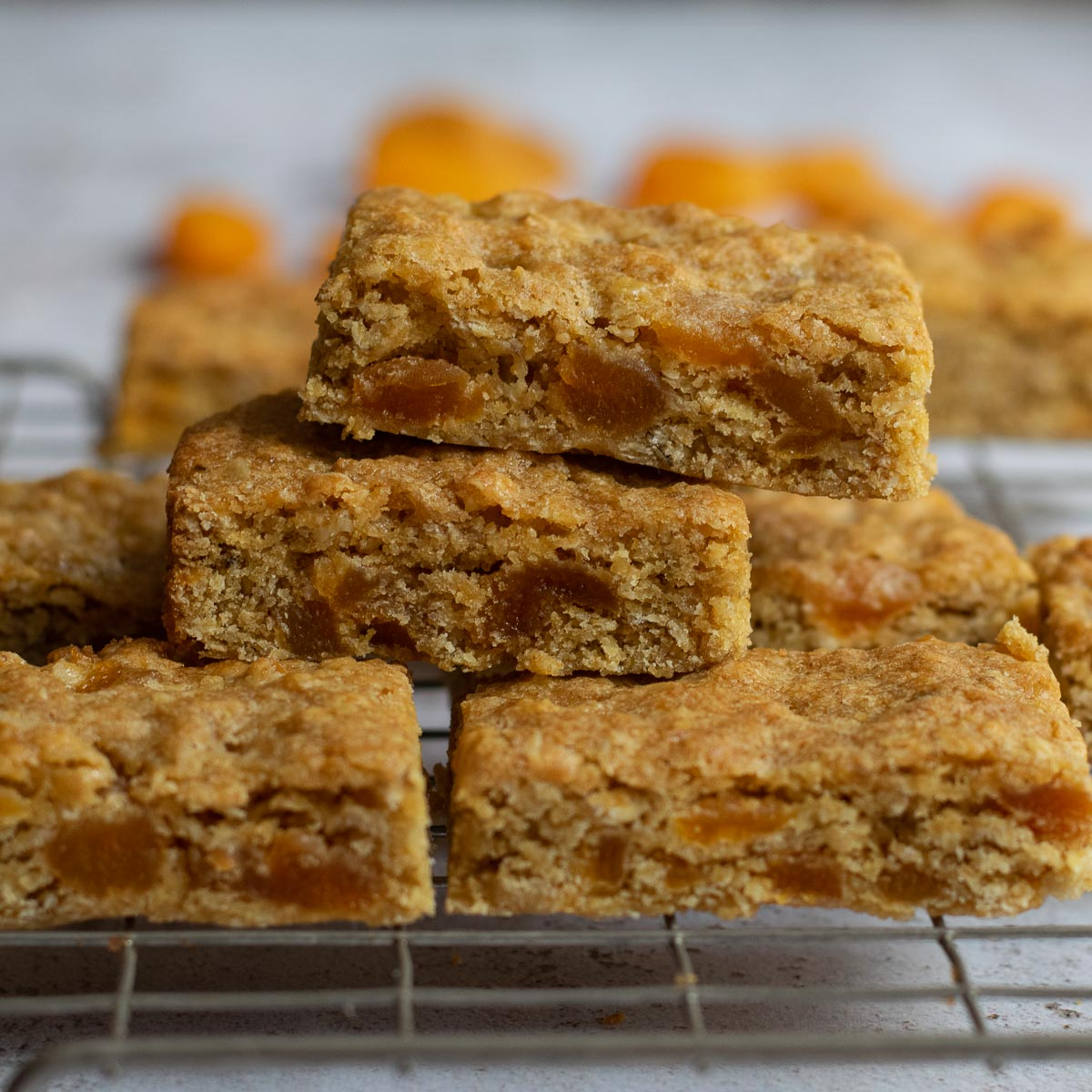 Stack of apricot oat bars on a wire rack with dried apricots in the background