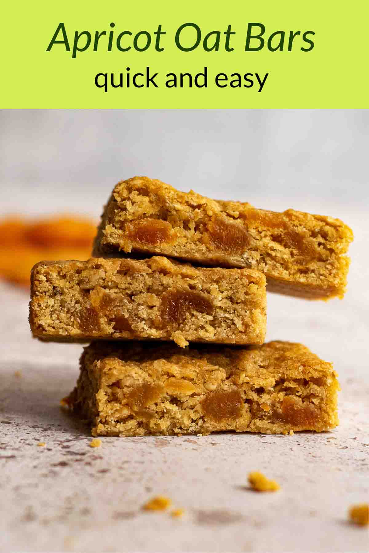 Stack of apricot oat bars with dried apricots in the background