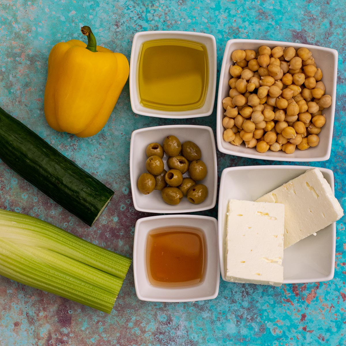 Ingredients for Feta Chickpea Salad on a blue background